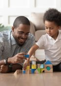 Black man playing with blocks with a young child